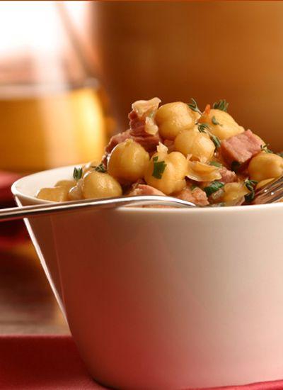 Garbanzos con jamón. Las tapas son las pequeñas delicias que alegran cualquier bar español. Con ellas, picar alcanza el estatus del arte. Sirva estos garbanzos con otros platos pequeños de tortilla de papas, calamares apanados y camarones al ajillo.