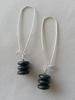 """Hand forged 19 gauge Argentium sterling silver long kidney-shaped earrings featuring a dangle stack of three matte black Czech glass disc beads.     These earrings measure nearly 5cm long and have longs of swing.  These kidney-shaped ear wires and made in a mirror image so that the fastengings face inwards towrads the neck when worn (for those who appreciate the little details). Make a statement!  Tamsin says: """"Keeping my designs ssAssi - simple, stunning, Affordable, stylish…"""
