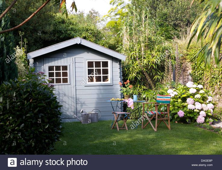 Download this stock image: Table and chairs on lawn in front of pale blue shed in French country garden in summer with pink hydrangeas against wall - DAGE8P from Alamy's library of millions of high resolution stock photos, illustrations and vectors.