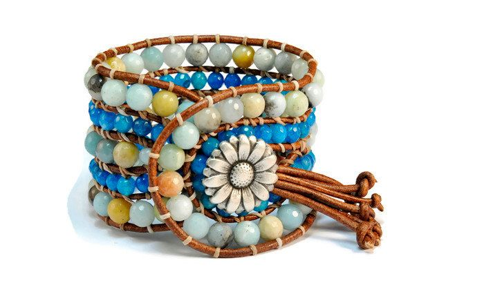 5 strands women's bracelet is crafted from a center of amazonite semiprecious stone. A strand of jade blue surrounds the center and a strand of amazonite finishes the design. Amazonite and jade blue are framed by natural brown leather woven together with beige wax cotton cord. This gorgeous design also features a floral metal, lightly oxidized button closure to signature our boho style collection.