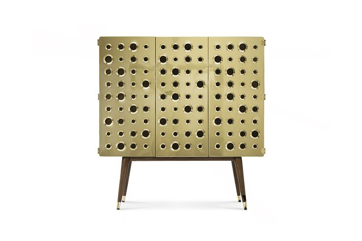 "If you are a fan of the James Bond world, you will certainly be dazzled with this golden eye‐catching piece. We named this cabinet ""Monocles"" and it is 100% prepared for Martini and Gin bottles. It is made in solid walnut wood and brass with knurled details. Circles are engraved on the sides and the back in the walnut wood, while three golden doors fulfill the setting with a kind of 'kiss kiss bang bang' spirit."