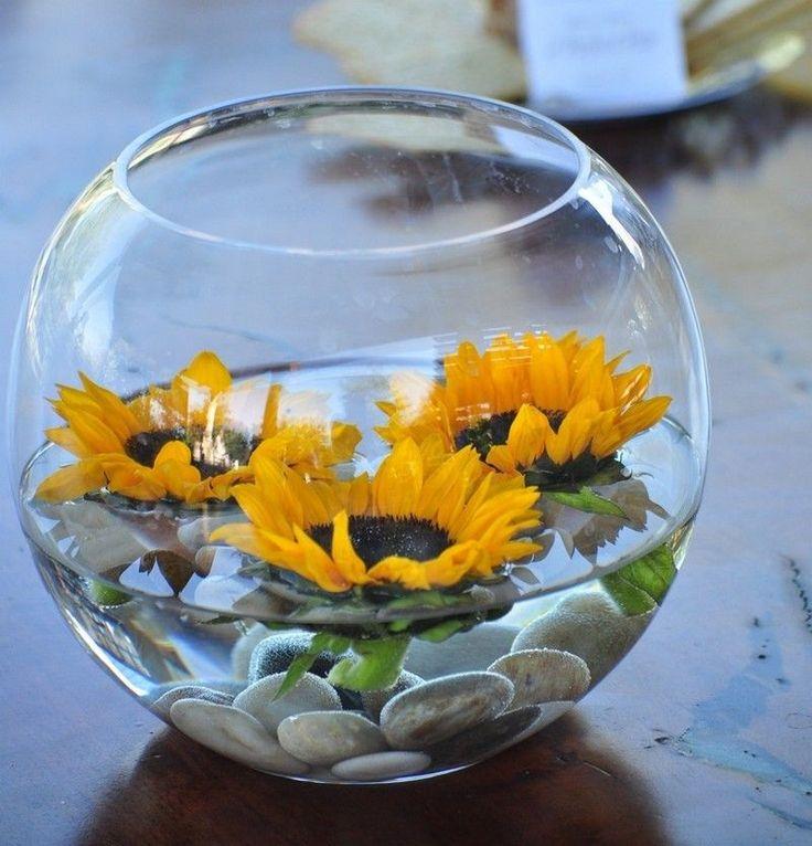 arrangement de fleurs de tournesol et galets dans un vase en verre rond