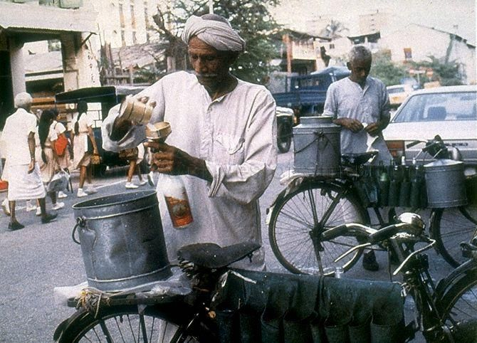 Indian man selling goat's milk from a bicycle at Serangoon Road.