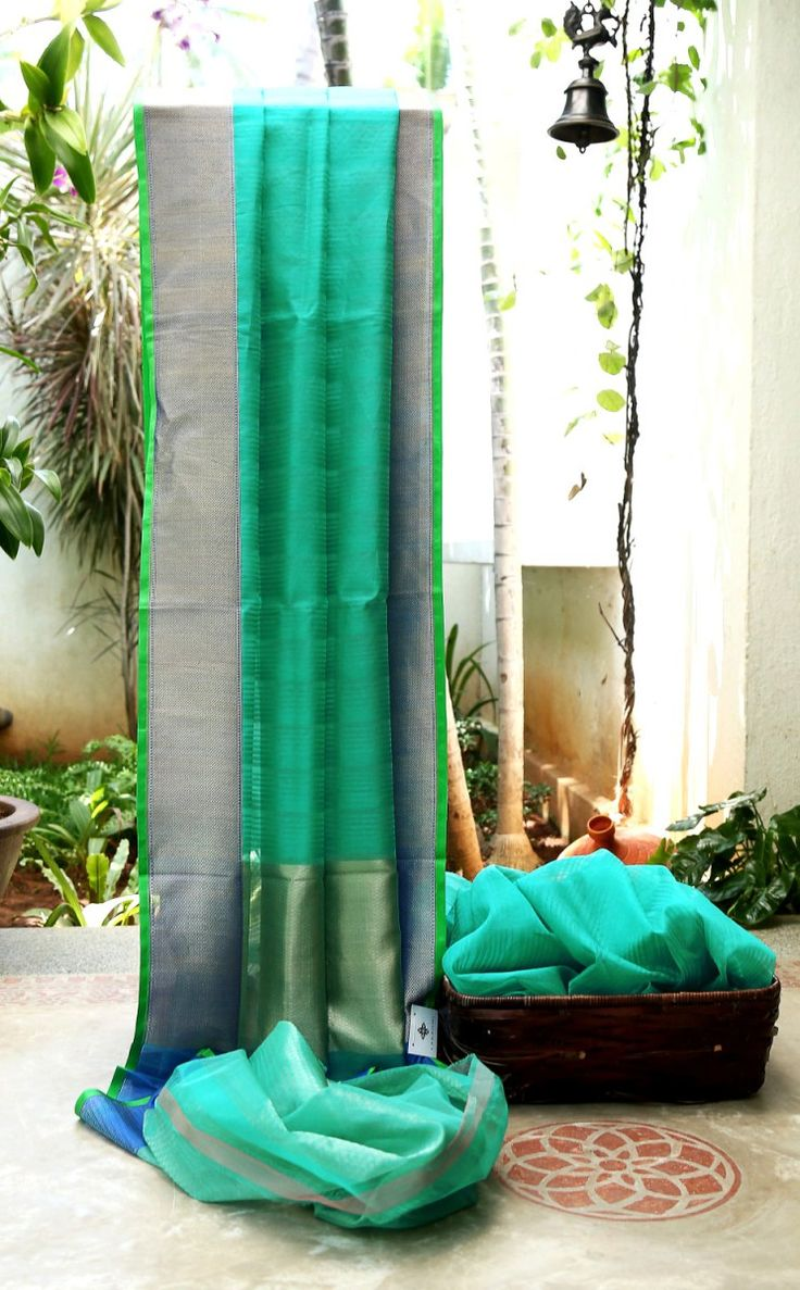 TURQUOISE GREEN SOUTH KORA SILK HAS COMPLIMENTING ROYAL BLUE WITH GOLD BORDER AND PALLU WHICH GIVES THE SAREE AN ELEGANT FINISHING LOOK.