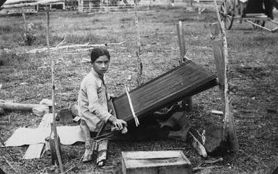 Potret seorang perempuan karo menenun kain khas karo | 1910-1930 | Een Karo Batak weefster achter een weeftoestel