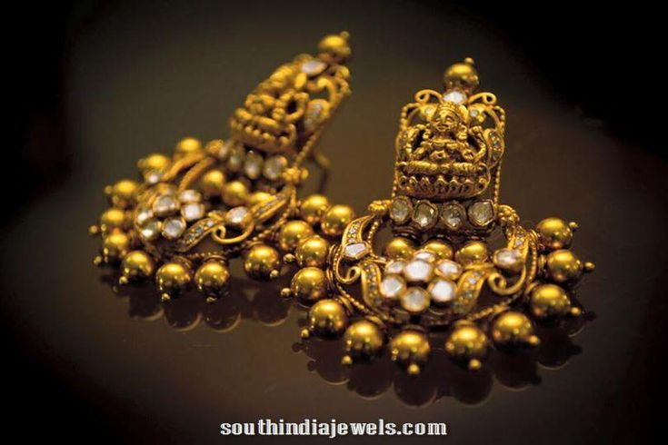 Classic gold antique temple jewellery earrings studded with white stones. For inquiries please contact Diamond Facets,099455 10049.