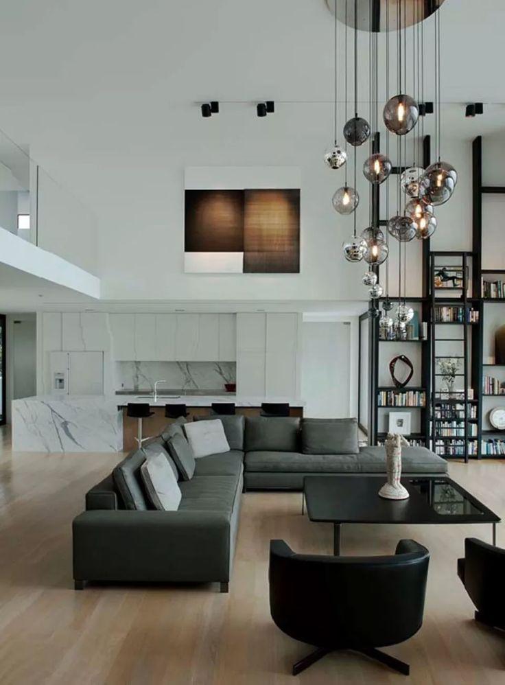 Soggiorno ultra-moderno in un ambiente open space con soffitti molto alti. Divani neri, pavimenti in legno chiaro e particolare illuminazione