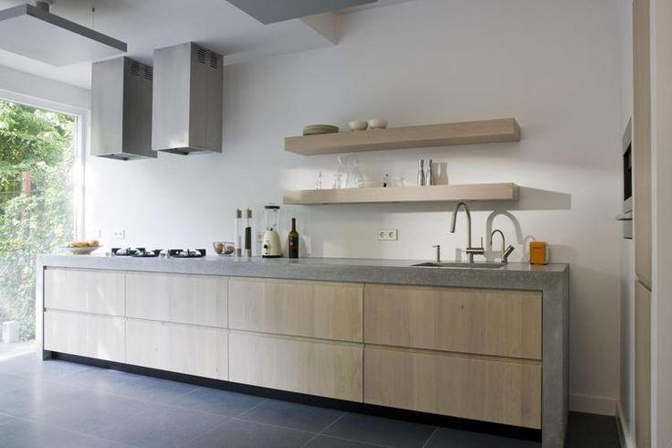 The Living Kitchen B.V. by Paul van de Kooi. Moderne keuken met betonnen keukenblad. Door het robuuste betonnen aanrechtblad krijgt deze moderne houten keuken een stoer uiterlijk. Het keukenblad loopt aan de zijkanten door tot op de grond. Er is in deze keuken veel bergruimte ontstaan door de diepe en brede lades. Hierdoor hoeven er geen bovenkastjes geplaatst te worden, maar volstaan een paar dikke planken. De twee vierkante afzuigkappen maken het plaatje helemaal af!