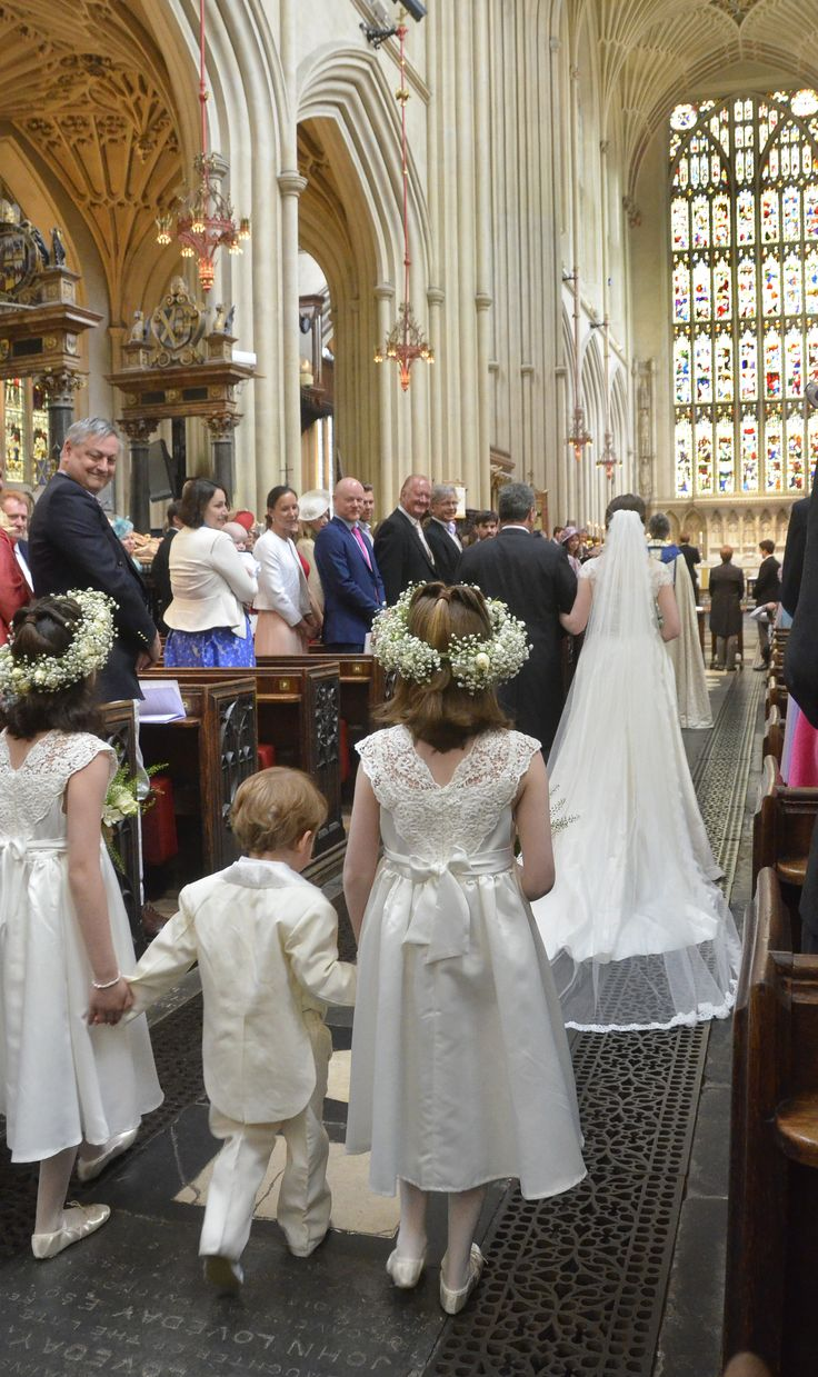 Cute white bridesmaids with gysophila crowns for an English wedding at Bath Abbey. Marianne wears Stewart Parvin classic lace strapless wedding dress with train and detachable skirt from Carina Baverstock Couture luxury designer bridal boutique Bradford on Avon, for her elegant Wiltshire wedding. Elegant country house Ilford Manor British wedding in England.  Image ©️ Dan Pix Wedding Photography