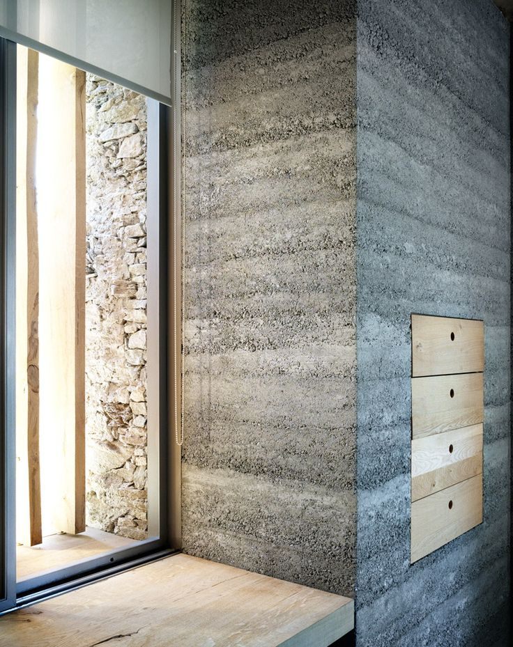armando ruinelli: redevelopment of a barn, soglio/smooth interior concrete wall meets rustic exterior stone wall
