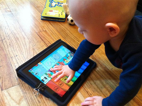 A binder clip keeps baby from pressing the iPad Home Button.