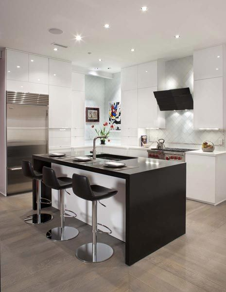 Deceptively simple looking, this contemporary kitchen employes a variety of materials and textures—stainless steel appliances, honed granite counters, glossy cabinets, wood-grain floors running in two different directions—to create sophisticated style.