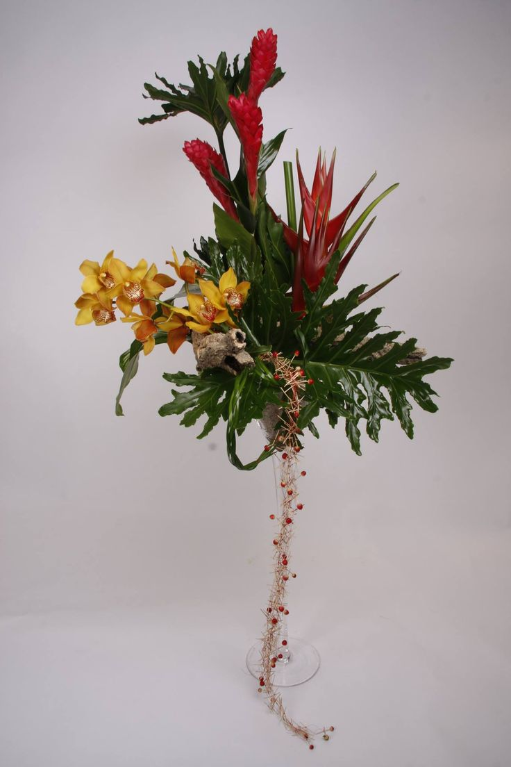 Spectacular tropical arrangement of Ginger flower, heliconia stem of yellow cymbidium orchid with vellum leaves and braided miniature wood sticks in a 3 feet high martini vase