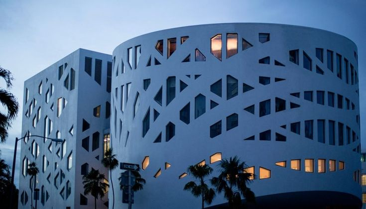 OMA claims to have taken inspiration from Frank Lloyd Wright's New York Guggenheim for the building's design, which features smooth white concrete facades. These are perforated by bands of irregularly shaped windows.