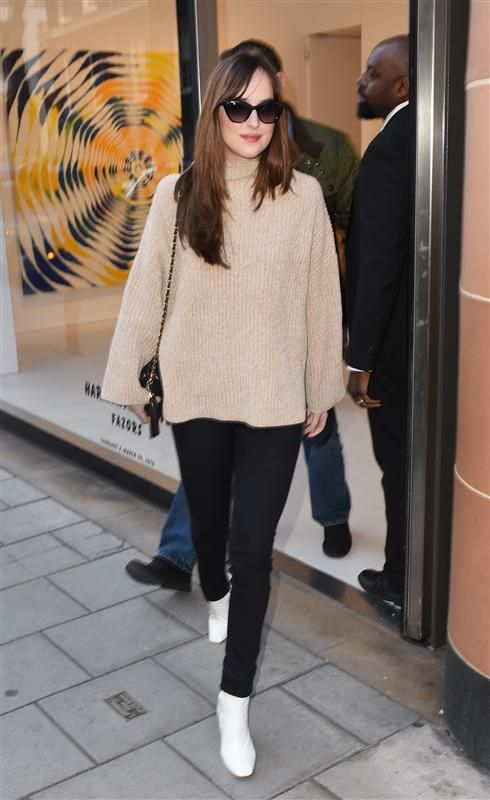 Dakota Johnson stepped out in style in London on Feb. 9, 2016, wearing an oversized nude turtleneck sweater, black skinny jeans and white ankle boots.