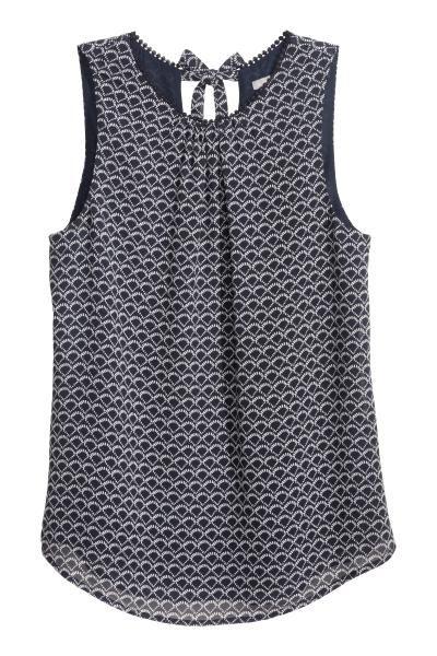 Blusa de gasa sin mangas: Blusa de gasa con detalles de encaje en el cuello, cierre de lágrima con tiras de anudar en la nuca y bajo redondeado. Forrada. Sin mangas.