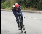 316b: A British road cyclist appears focused as he takes a curve. This is due to his framing in the center of the image with a sense of intensity in his face. The neutral background causes the focus of the image to be entirely on him.