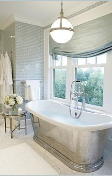 Photo: Mabley Handler  Grey glass subway tiles wallpaper the walls and compliment the shiny metal stand alone tub in this chic master bath. (above)