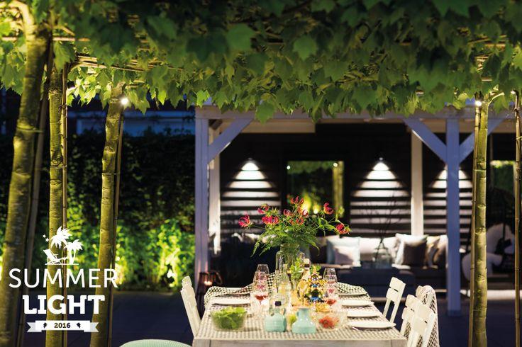 In de reeks SUMMER LIGHTS deze sfeervolle tuin met daarin buitenspot MINI SCOPE tussen de platanen om de mooi gedekte tafel uit te lichten en in de overkapping wandlamp ACE DOWN DARK.