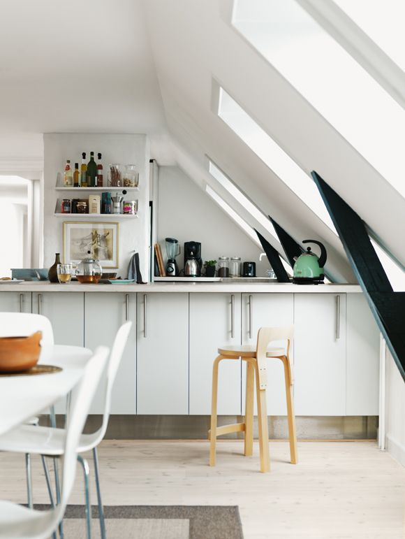 This kitchen was once a dark and unwelcoming attic. Now it can see the light of day thanks to five VELUX roof windows. The white-painted windows complement the white kitchen and furniture perfectly, and form a striking contrast between the black rafters.