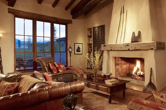 Vaulted living room with ceiling beams, stucco fireplace and burnt orange and tan furnishings -- Miller Architects, ctmarchitects.com -- North Star Ranch, Colorado -- #NorthStarRanch