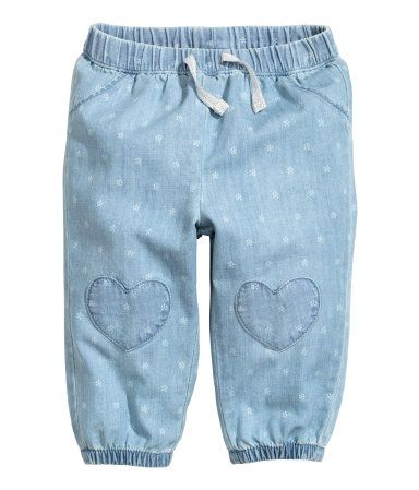 Light denim blue. Pull-on jeans in soft, washed denim with a printed pattern. Elasticized drawstring waistband, mock pockets at front, heart-shaped