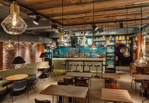 Tijolo rústico, revestimento madeira, azulejos turquesa, ladrilho hidráulico, bancos e luminárias industriais, spots