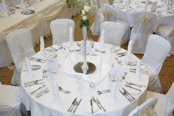 Table set up with white roses in tall vase