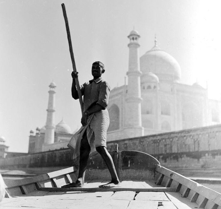 A boatman propels his boat with a single oar along the Jumna river, in the background rises the Taj Mahal