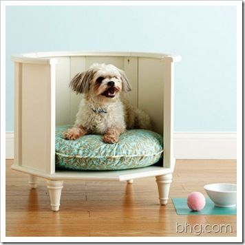 An old round nightstand or unused side table has been turned into an adorable pet bed.