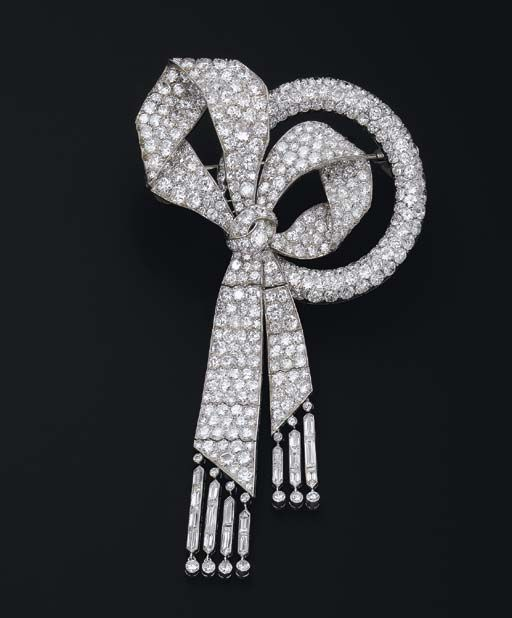 AN EXQUISITE ART DECO DIAMOND 'BOW' BROOCH, BY BOUCHERON   The pavé-set diamond bow with accentuated ribbons and baguette-cut diamond tassels to the pavé-set diamond ring-shaped detail, circa 1925, 11.0 cm long, with French assay marks for platinum and gold  Signed Boucheron, no. 27856