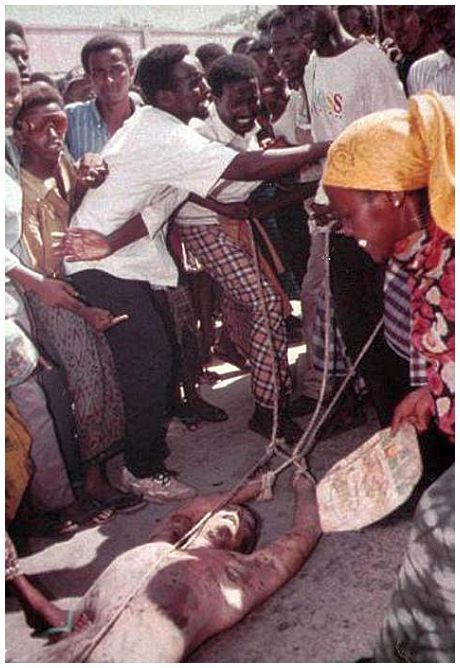 The body of a U.S. serviceman is dragged with ropes through the dusty streets of war-torn Mogadishu, Somalia, on Oct. 4, 1993. The dead soldier was one of five Americans killed during the first day of a major U.N. assault on warlord Mohamed Farah Aidid's military command.: