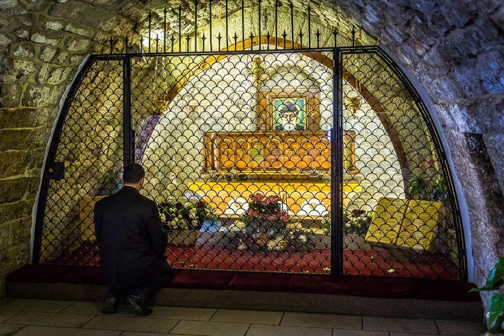 Mężczyzna modlący się przy grobie świętego, we wnętrzu klasztoru.