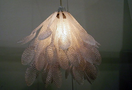 Here, 300 plastic spoons were patterned and textured using a soldering gun to drill holes and then artfully joining them together to form a simple yet sophisticated use of the ordinary to form an extraordinary petal pendant light.