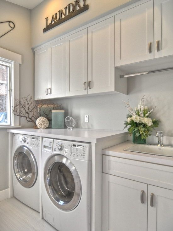 Clean, light and white laundry with overhead cupboards
