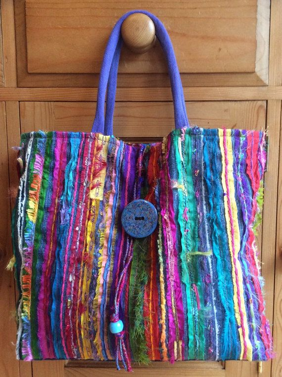 Bright and cheery hand-made tote bag, made with up-cycled denim jeans and sari silk with added strips of assorted multicoloured yarns. Fully lined