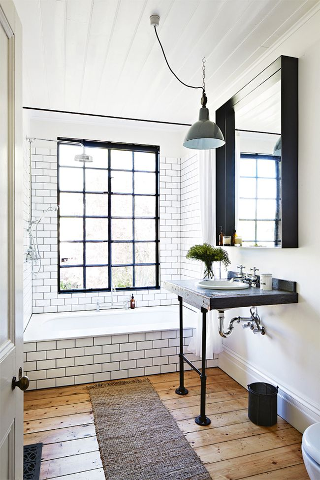 This swoonworthy bathroom has subway tile, a cement slab sink with pipe accents and warm wood flooring.