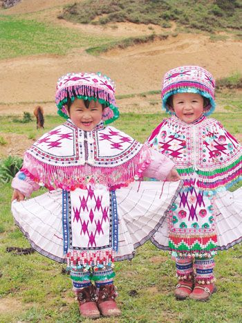 """Crianças da etnia Hmong, vestidas em trajes tradicionais. Os hmong são um grupo étnico asiático, originário das regiões montanhosas do sul da China (especialmente da região do Guizhou), do norte do Vietnã e do Laos. São considerados, na China, um dos grupos Miao, termo que significa """"arroz cru"""" e designa várias populações nômades pouco integradas no país. Os hmong chamam-se comumente a si próprios """"povo da montanha"""". Falam a língua hmong, um idioma da família hmong-mien."""
