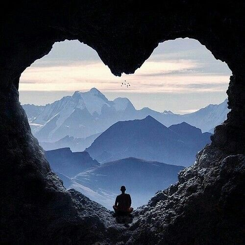 ⭐Love this view⭐ A lone man sits in the middle of a heart-shaped opening in a cave. In the distance, we can see snow-capped mountains and clear blue skies.: