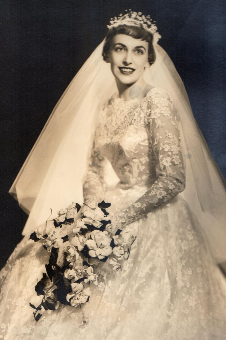 1950s Bride Wearing A Long Sleeve Lace Ball Gown, Mid Length Veil, & She Holds A Bouquet Of Beautiful Gardenias! This Could Very Well Be A Bride Today!!