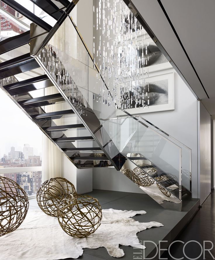 A custom-made Swarovski-crystal light fixture hangs above a stainless steel-and-glass staircase; the bronze spheres are by Hervé Van der Straeten, and the photographs are by Sam Samore.   - ELLEDecor.com