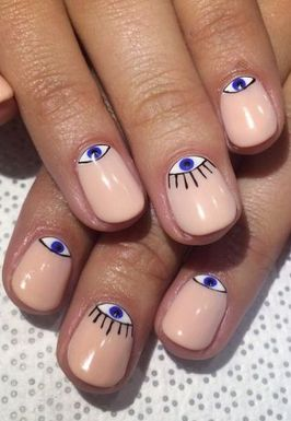 For this evil eye Halloween look, paint your nails nude. Add white to your half moons and let dry. Then add blue circles to the center to create the irises. Use a thing black brush to outline each eye and add eyelashes to your statement nail. Finish with a clear topcoat.