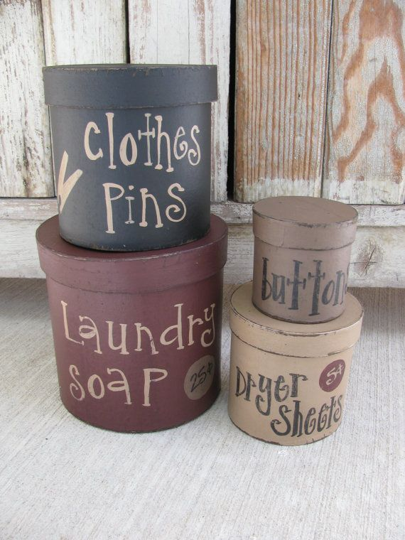 Primitive Laundry Room Set of 4 Round Stacking Boxes. I love these boxes. They are perfect for dressing up that mudroom/laundry room/washroom! What better way to do so then adding these neat and useful boxes to a shelf, cabinet, or top of your dryer. The colors are burgundy, dark navy, khaki tan, and mustard. OR now Im offering a new color scheme of Burgundy, Black, Khaki Tan and Mississippi Mud. The bottom box has laundry soap 25 cents, next is clothes pins, then dryer sheets 5 cen...