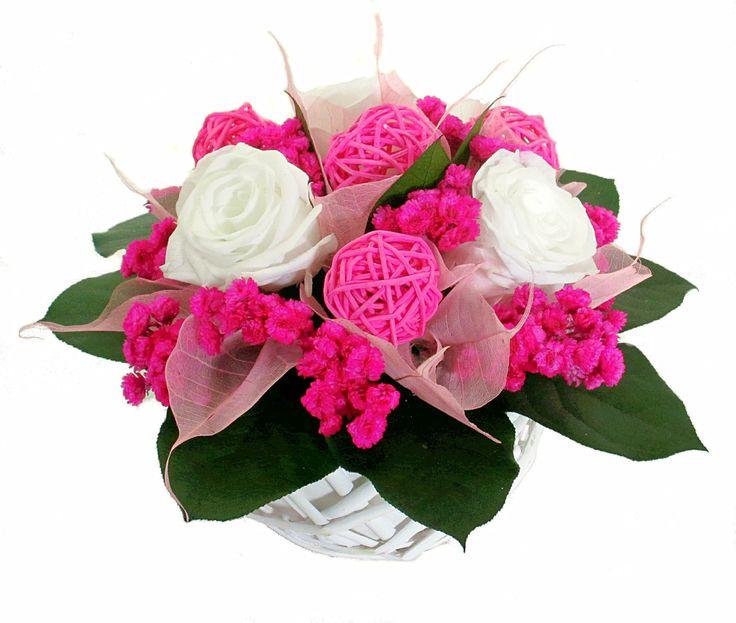 Un petit panier en osier avec de la rose blanche stabilisée et de l'immortelle séchée rose.