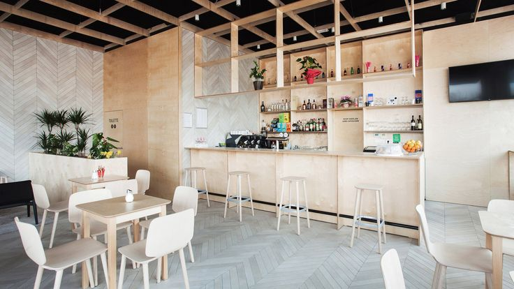Slovenia-based architect Sanja Premrn paired simple plywood panels with pale, chevron-patterned tiling to create the angular geometries of this cafe bar
