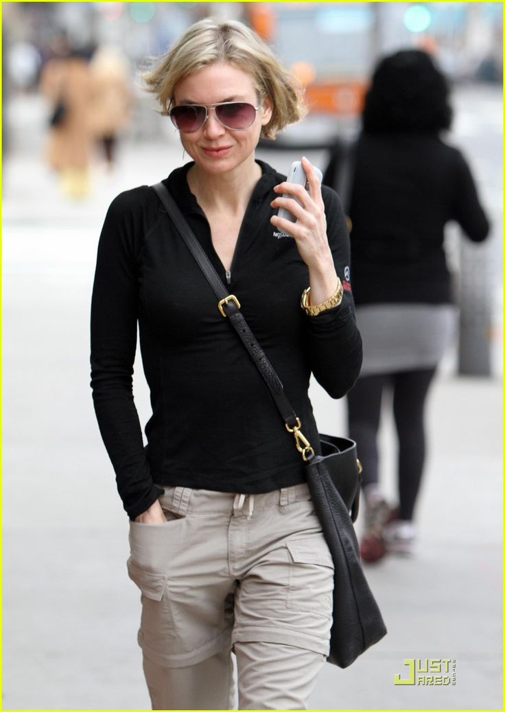 Rene Zellweger in kakis, a black fitted athletic zippered pullover and messenger bag