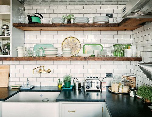 farmhouse-style open kitchen with soapstone counters and a brass Watermark faucet