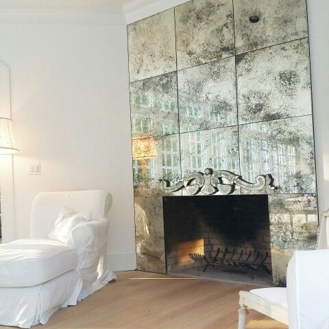 Floor to ceiling mirrored Fireplace with one arm white denim lounge chair @rasccouture @officialshabby Waiting to be transformed in all shabby chic style soon... #ThePrivateHouse #minimal Photo Credit: Angeliki Karamina