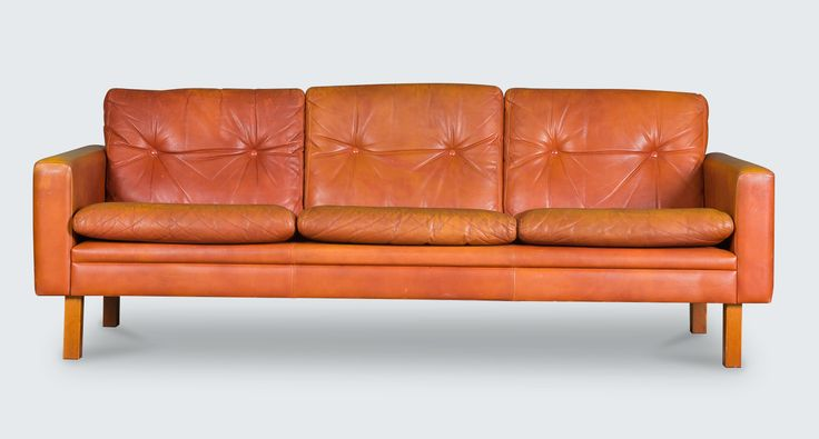 Beautiful 3-seater sofa in a striking cognac tufted leather and hardwood legs. The design and colour speak to the character of this piece. Just lovely!