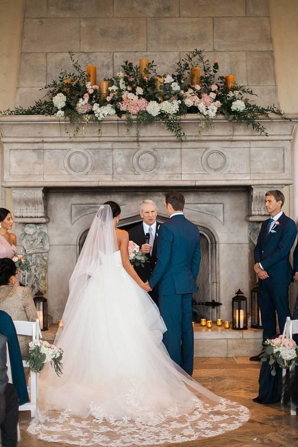 Ceremony in front of fireplace at Villa del Lago in Austin